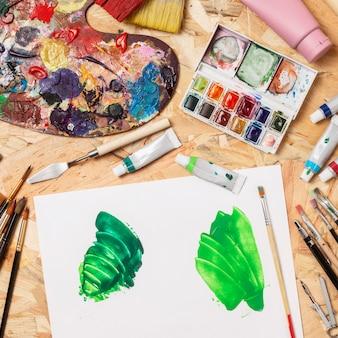 緑のペンキとカラーパレットのキャンバス