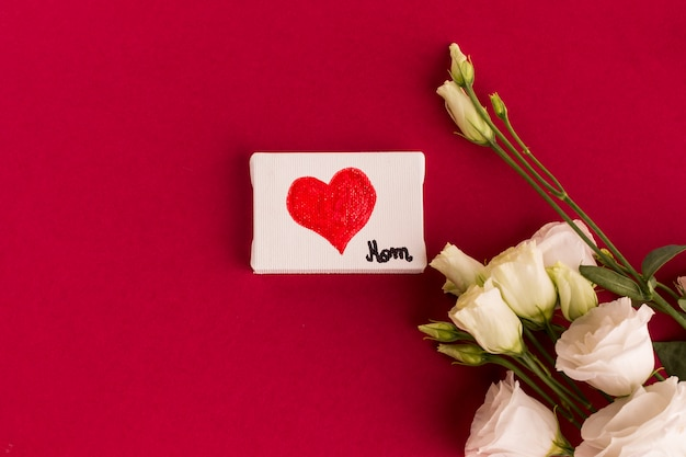 Canvas with heart near bouquet of flowers