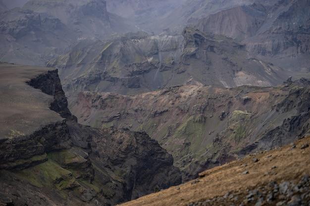 Каньон с разноцветными слоями скал и холмов.