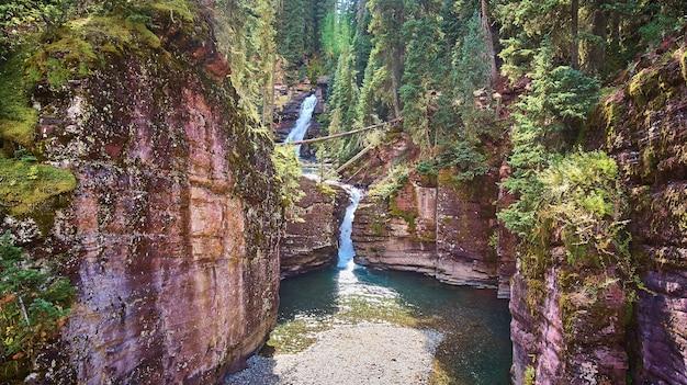 滝と地衣類の岩のある峡谷