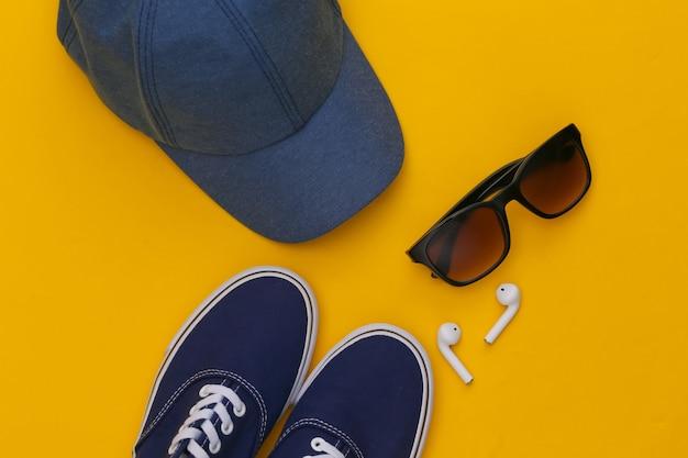 노란색 배경에 모자와 선글라스, 무선 이어폰, 운동화.