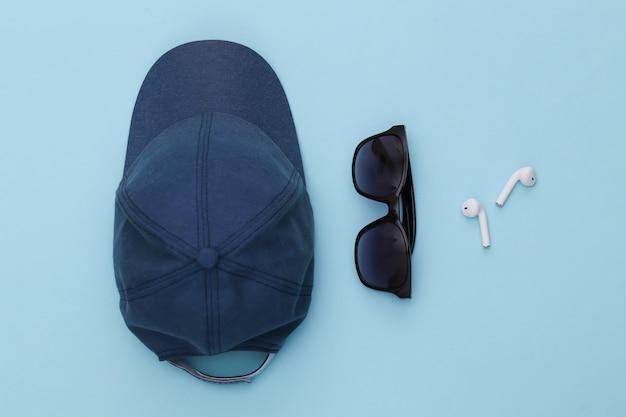 모자와 선글라스, 파란색 배경에 무선 이어폰.