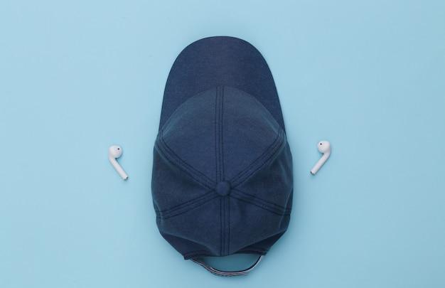 파란색 배경에 모자와 무선 이어폰.