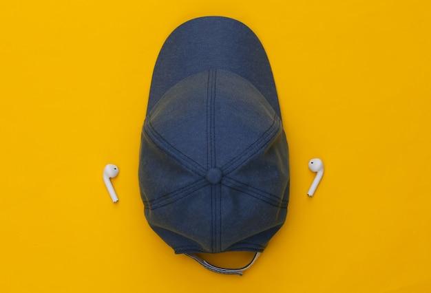 노란색 배경에 모자와 무선 이어폰.