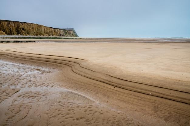 フランスの曇り空の下でビーチと海に囲まれたキャップブランネズ