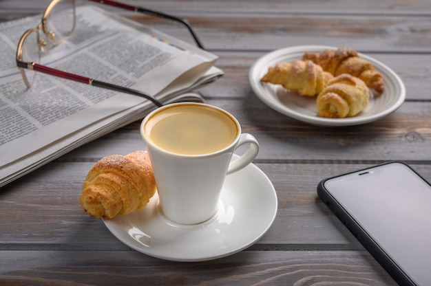 Cap of coffee and homemade cookies bagels on wooden surface near smartphone newspaper and glasses
