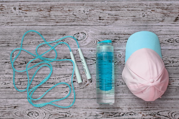 Cap, jump rope and water bottle on wooden floor. sports style. flat lay.