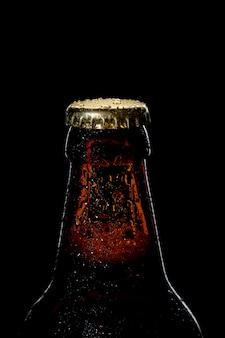 검은 배경에 맥주 병 근접 촬영의 모자 프리미엄 사진
