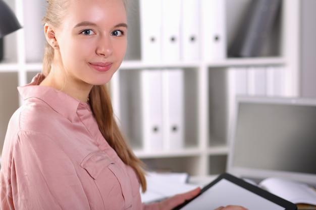 フロントラップトップの有能な女の子のオフィスはタブレットを保持しています。