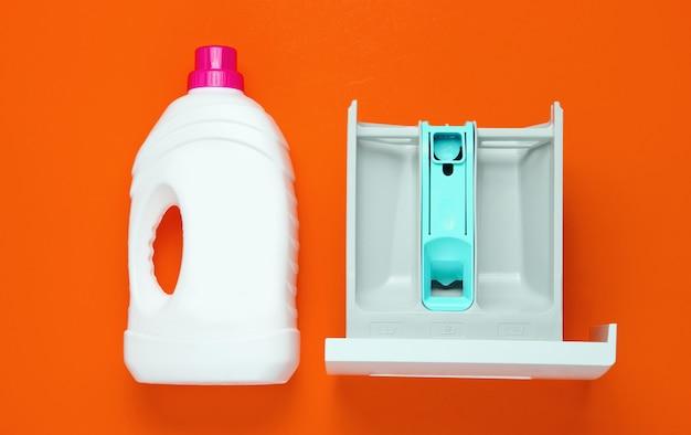 Емкость стиральной машины для порошка, бутылка геля для стирки на оранжевом фоне. вид сверху, плоская планировка