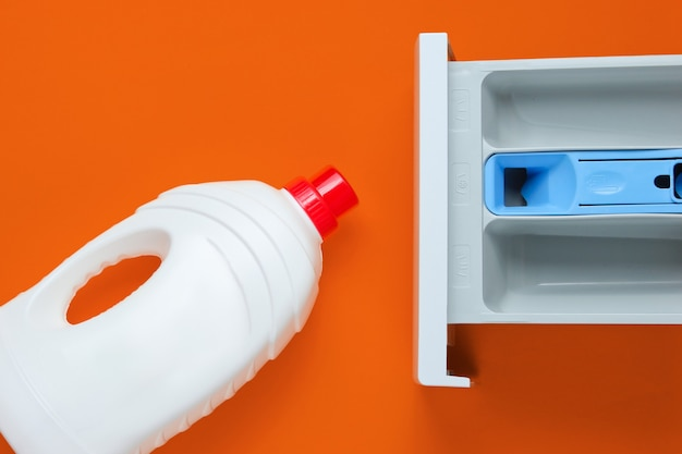 Capacity of washing machine for powder, bottle of washing gel on orange background. top view, flat lay