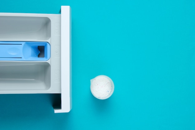 Capacity of washing machine for powder, measuring container with powder on blue table. top view, flat lay