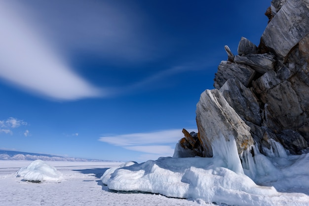 Cape burhan on shamanka rock in olkhon island covered with icicles in sunny march day. lake baikal with beautiful clouds