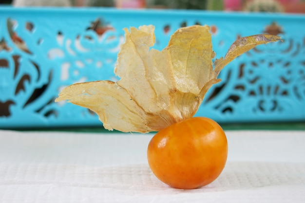 A cape gooseberry with its papery husk placing on the white paper on the table with the blue basket at the background