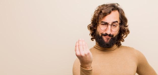 若者は、あなたの借金を支払うように言って、capiceまたはお金のジェスチャーを作る狂気の男を生やした!フラットカラーの壁に対して