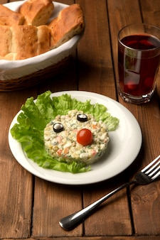Capital salad with olive eyes and tomato nose