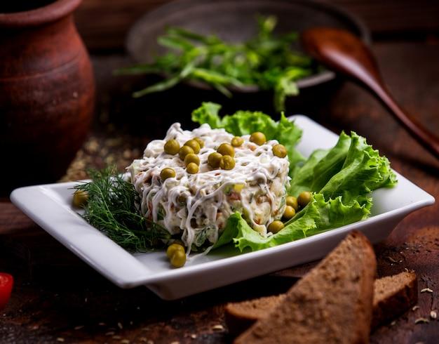 Столичный салат с горошком на столе