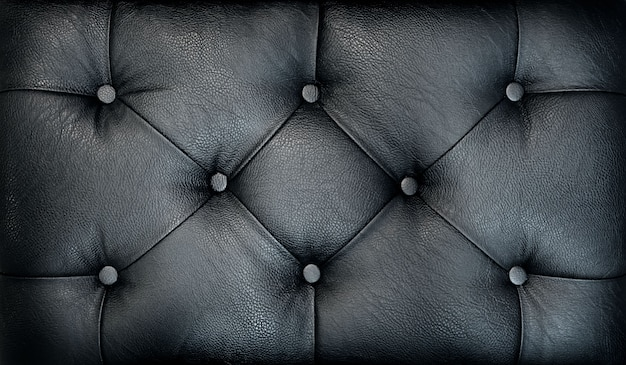 カウチスクリードレトロな暗いチェスターフィールドスタイルのキルト張りの室内装飾品の背景をクローズアップ。黒capitoneパターンテクスチャ背景