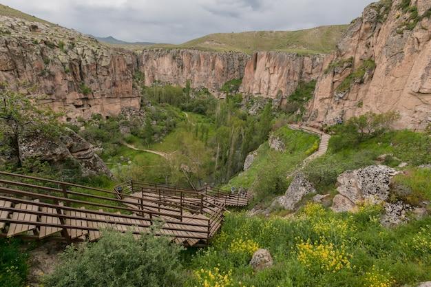 Каппадокия: скалистый каньон долины ихлара потрясающий летний пасмурный пейзаж. турция