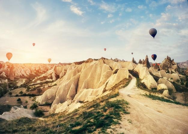 Горячий воздушный шар летая над ландшафтом утеса на cappadocia турции.