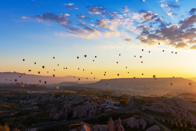 Цветастый горячий воздушный шар летая над красной долиной на cappadocia, анатолии, турции.