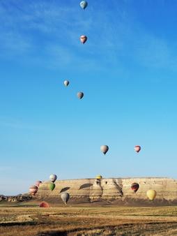 Красивый вид красочных горячих воздушных шаров летая над ландшафтом в cappadocia, турции.
