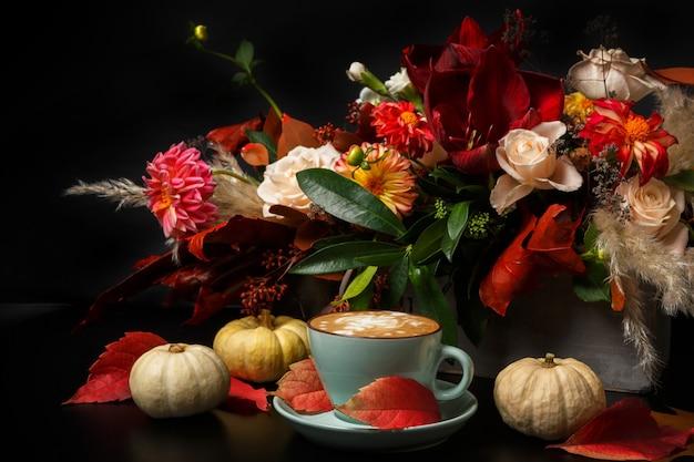 カプチーノと美しい花の花束の静物画。フラワーショップの構成。コーヒーカップ、黒い木製のテーブルにカボチャ。花屋の芸術と花のデザインコンセプト