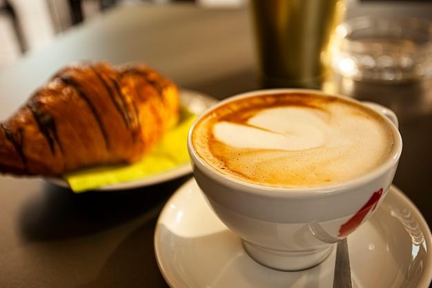 カプチーノとブリオッシュのディテール:伝統的なイタリアの朝食の象徴