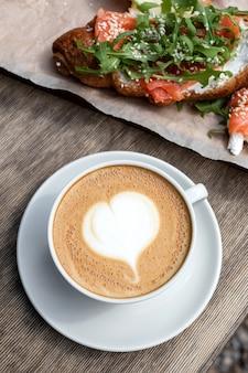 Завтрак с капучино и булочкой в кафе. американское утро. круассан с форелью и рукколой