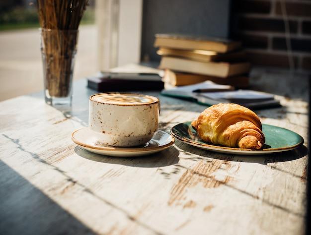 カプチーノとクロワッサンは、窓と本の山を背景にカフェのテーブルに横たわっています。朝日がテーブルに降り注ぐと、美しい影が現れます。おいしい朝食。