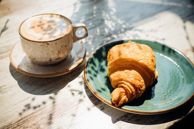 カフェのテーブルにはカプチーノとクロワッサンが。朝日がテーブルに降り注ぐと、美しい影が現れます。おいしい朝食。