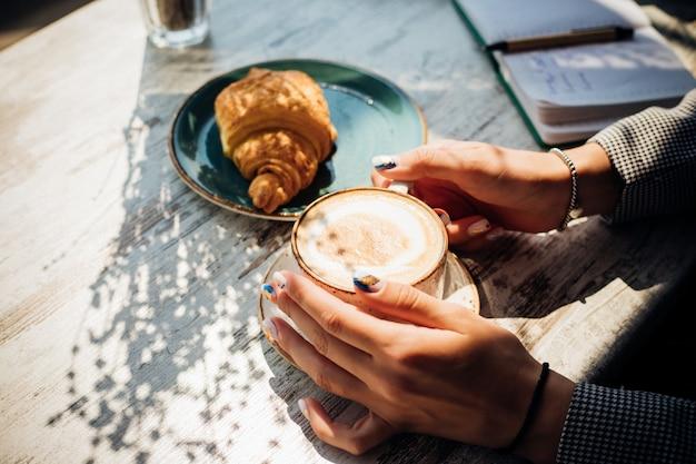 カフェのテーブルにカプチーノとクロワッサン。朝日がテーブルに降り注ぐと、美しい影が現れます。おいしい朝食。女性の手は一杯のコーヒーを持っています。