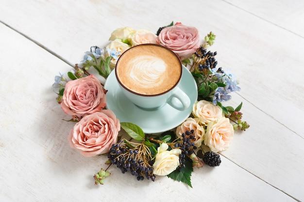 カプチーノと花の組成物。クリーミーな泡と青いコーヒーカップ、白い木製のテーブルで新鮮なドライフラワーサークル。温かい飲み物、季節のオファーのコンセプト