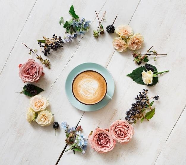カプチーノと花の組成物。クリーミーな泡と青いコーヒーカップ、白い木製のテーブル、トップビューで新鮮なドライフラワーサークル。温かい飲み物、季節のオファーのコンセプト