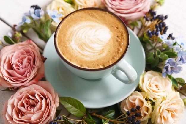 カプチーノと花の組成物。クリーミーな泡が付いている青いコーヒーカップ、新鮮なドライフラワーサークル
