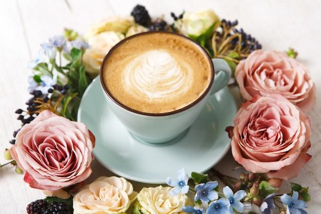 カプチーノと花の組成物。クリーミーな泡、新鮮なドライフラワーと青いコーヒーカップ