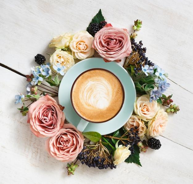 カプチーノと花の組成のクローズアップ。クリーミーな泡と青いコーヒーカップ、白い木製のテーブル、トップビューで新鮮なドライフラワーサークル。温かい飲み物、季節のオファーのコンセプト