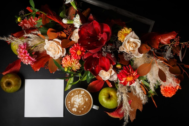Cappuccino and beautiful flowers still life. flower shop top view composition. coffee cup, apple, fresh and bouquet on black wooden table. florist art and floral design concept