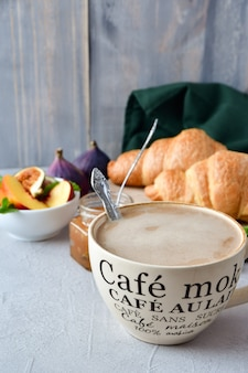 Cappuccino breakfast with croissant, fresh apple jam and fruit salad. breakfast menu