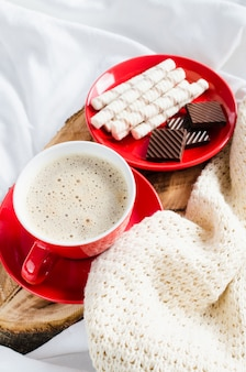 Cappuccino and chocolate on a bed with plaid.