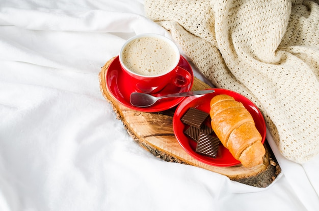 Cappuccino, chocolate and croissant on a bed.