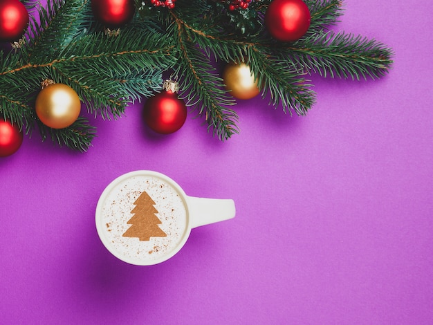Cappuccino and christmas gifts with pine branch on violet.