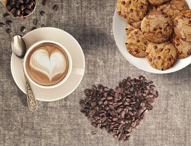 Cappuccino coffee beans in heart shape and home-baked chocolate chip cookies in a coffee house