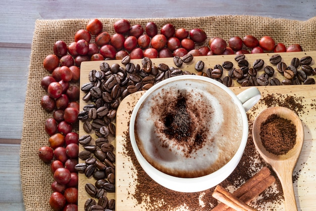Cappuccino coffee and coffee beans coffee cherry on wood top table