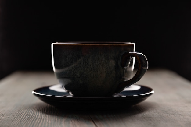 Cappuccino in coffee cup on dark background