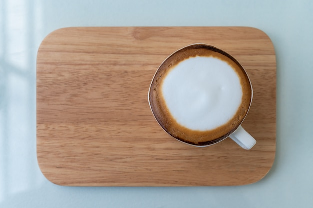 Cappuccino coffee cup on wooden plate