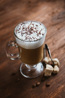 Cappuccino coffee in a glass on a brown wooden table