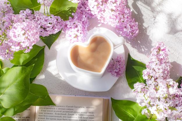Кофе капучино в чашке с книгой и веткой сирени на белой поверхности с тенями