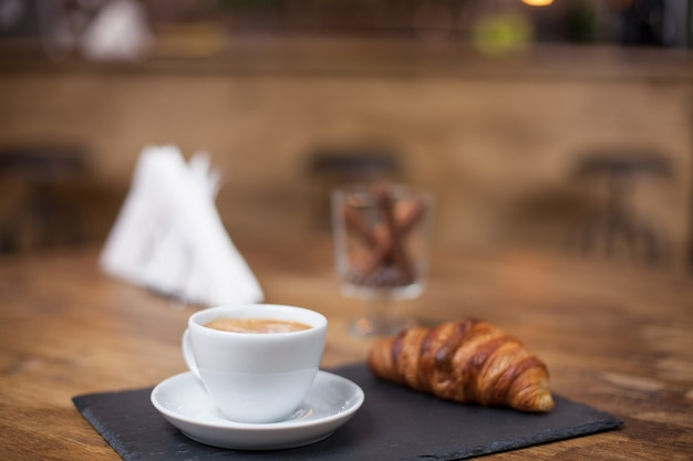 おいしいクロワッサンの横にある木製のテーブルの上の白いカップのカプチーノコーヒー。おいしいスナック。ヴィンテージコーヒーショップ。
