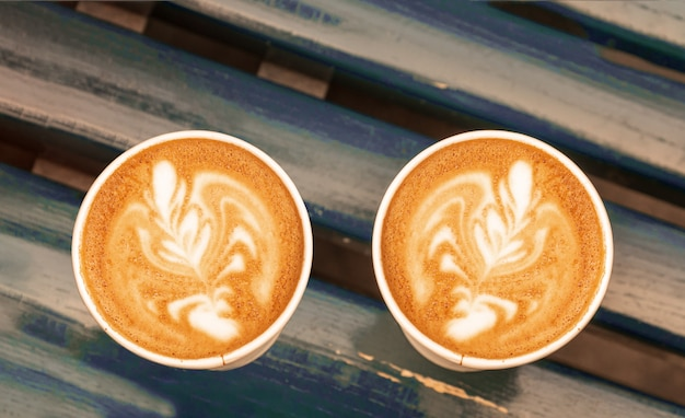 Cappuccino coffee latte art in paper cups on wooden bench, outdoor.